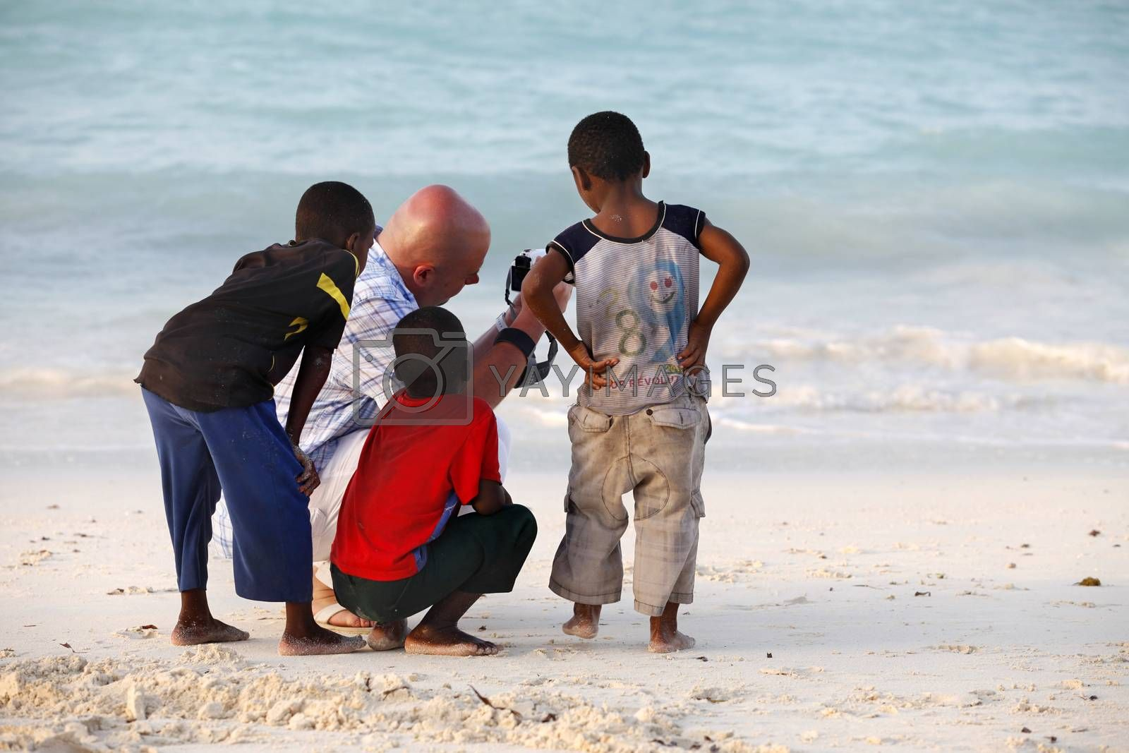 Nungwi, Zanzibar, Tanzania - January 9, 2016:  Large white man-tourist with African children on beach of village Nungwi. Zanzibar, Tanzania