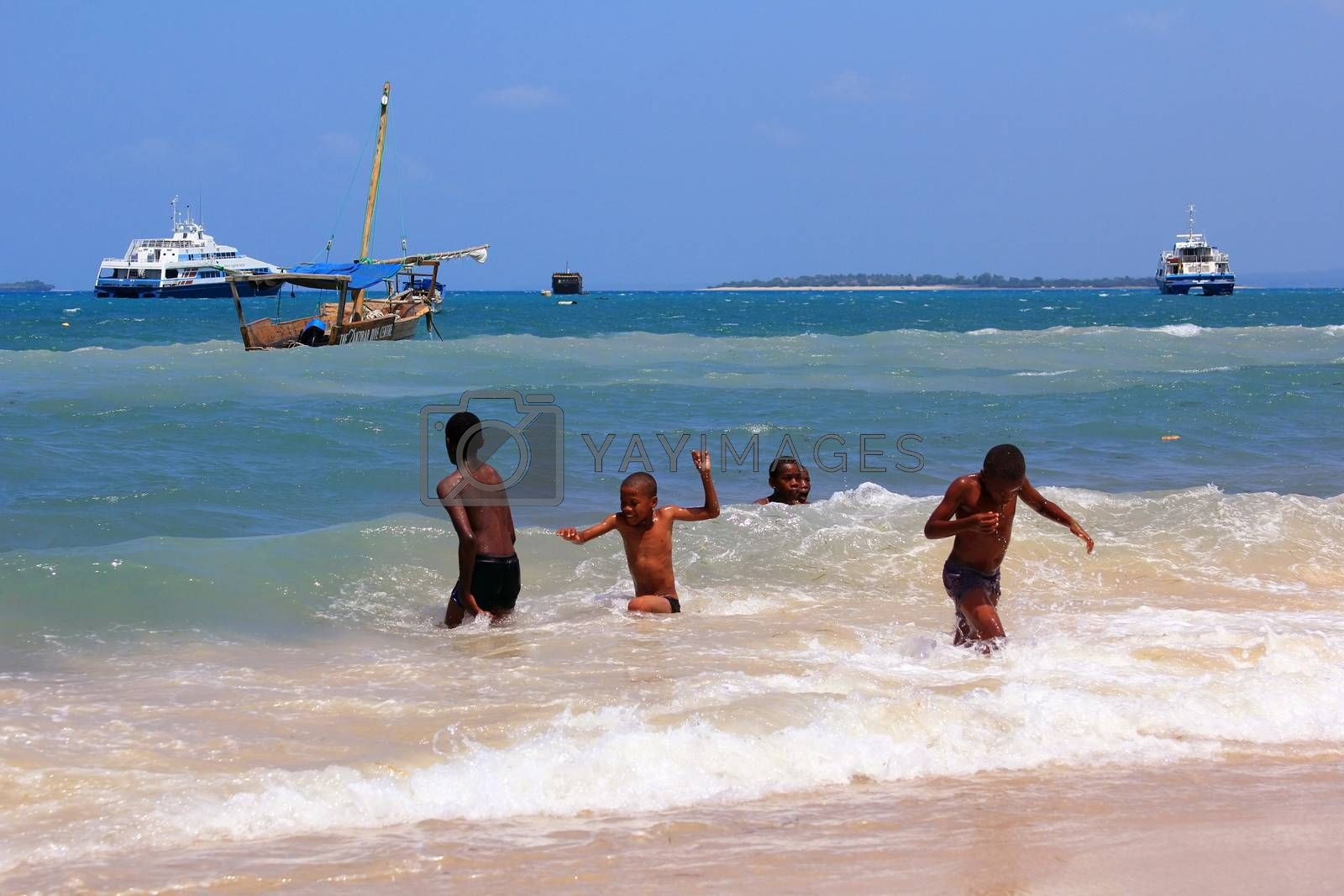 Zanzibar, Tanzania - December 30, 2015: Group of kids playing in the water on the beach of Stone Town. The capital of Zanzibar.