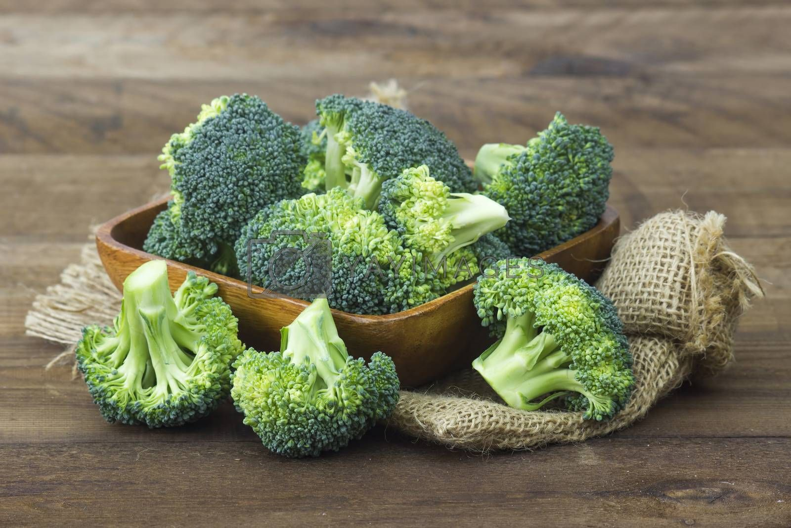 Raw broccoli in a bowl on wooden background