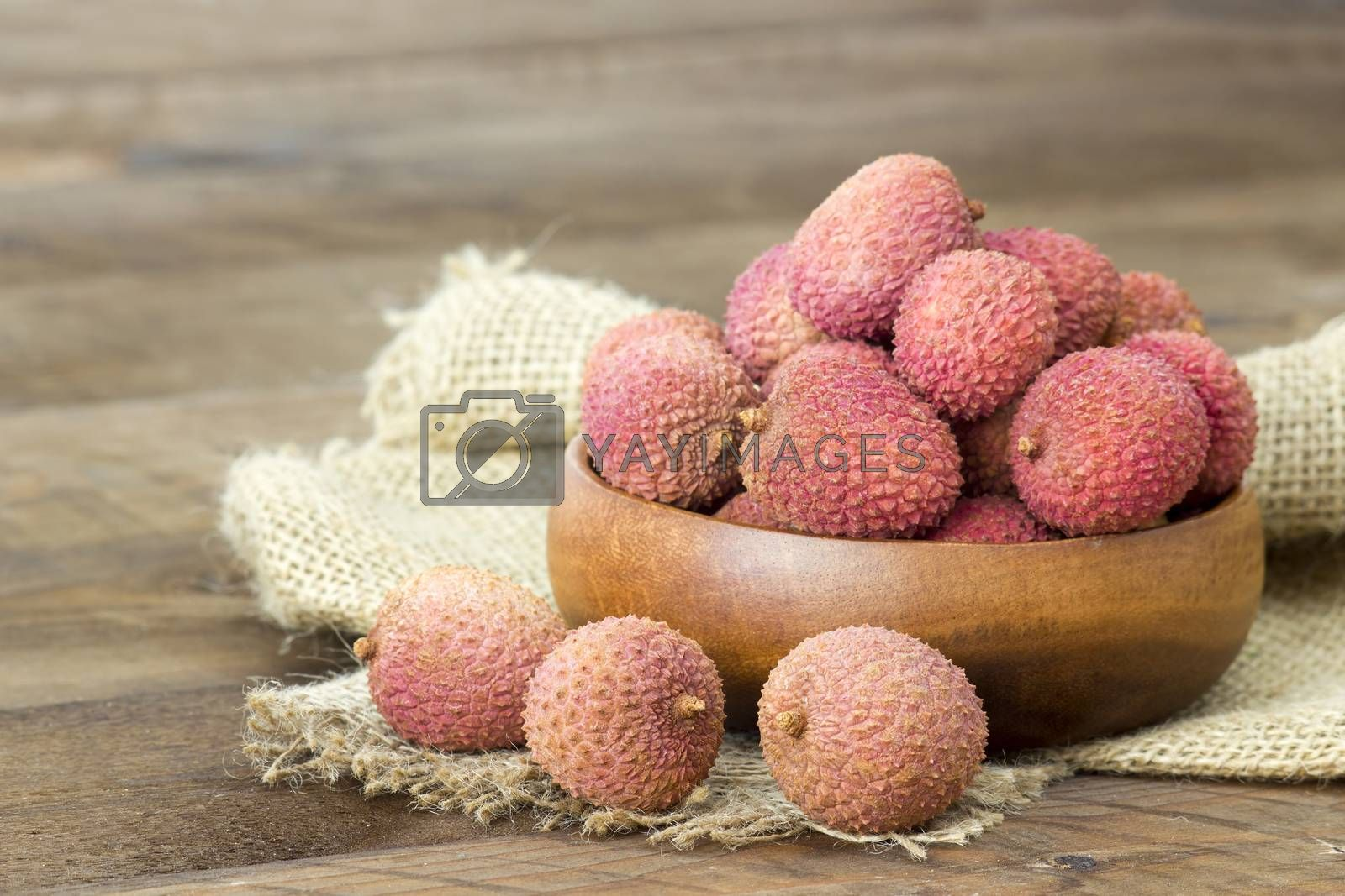 fresh lychees in a bowl  on wooden background
