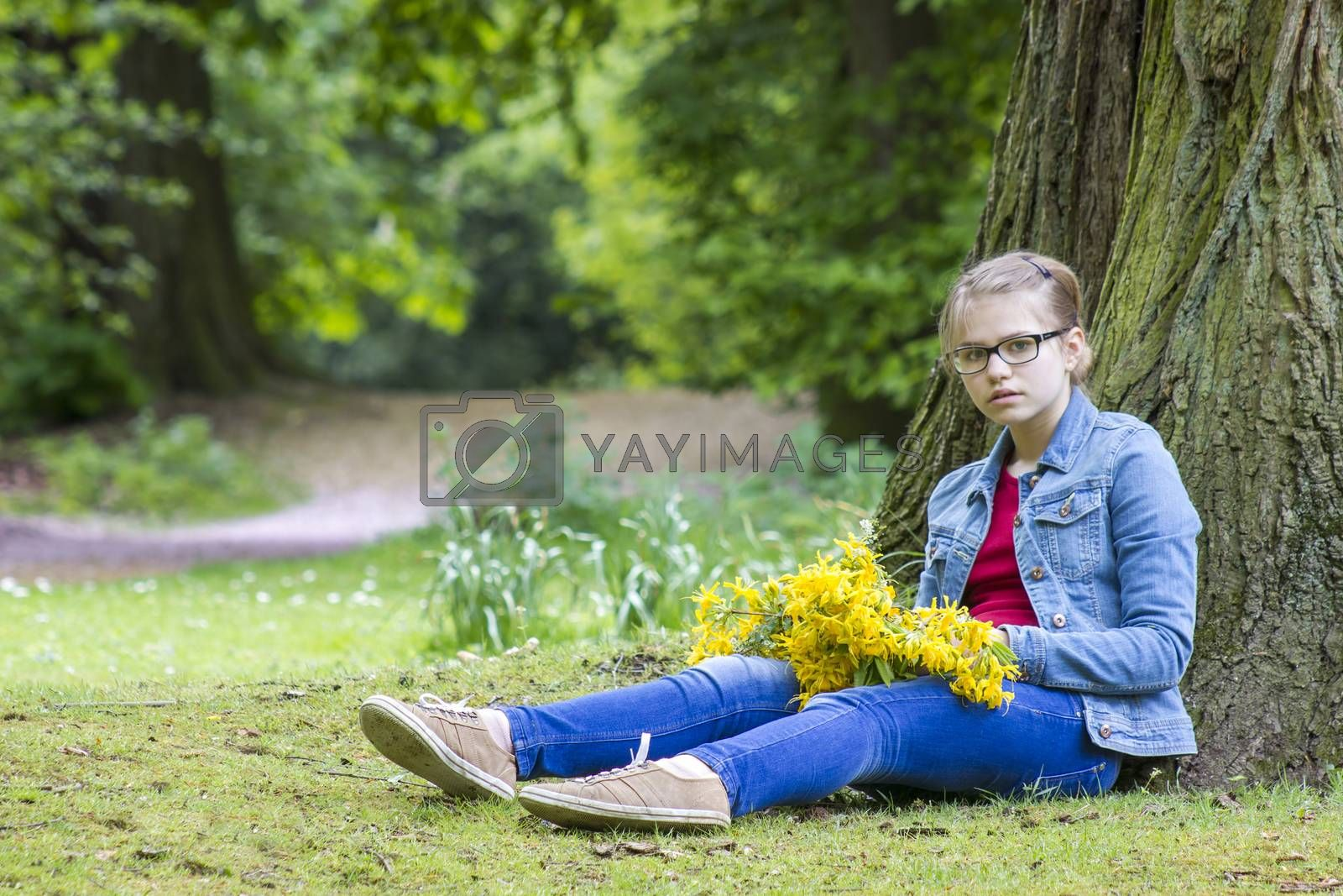 girl with big bouquet of spring flowers sitting in the park by miradrozdowski