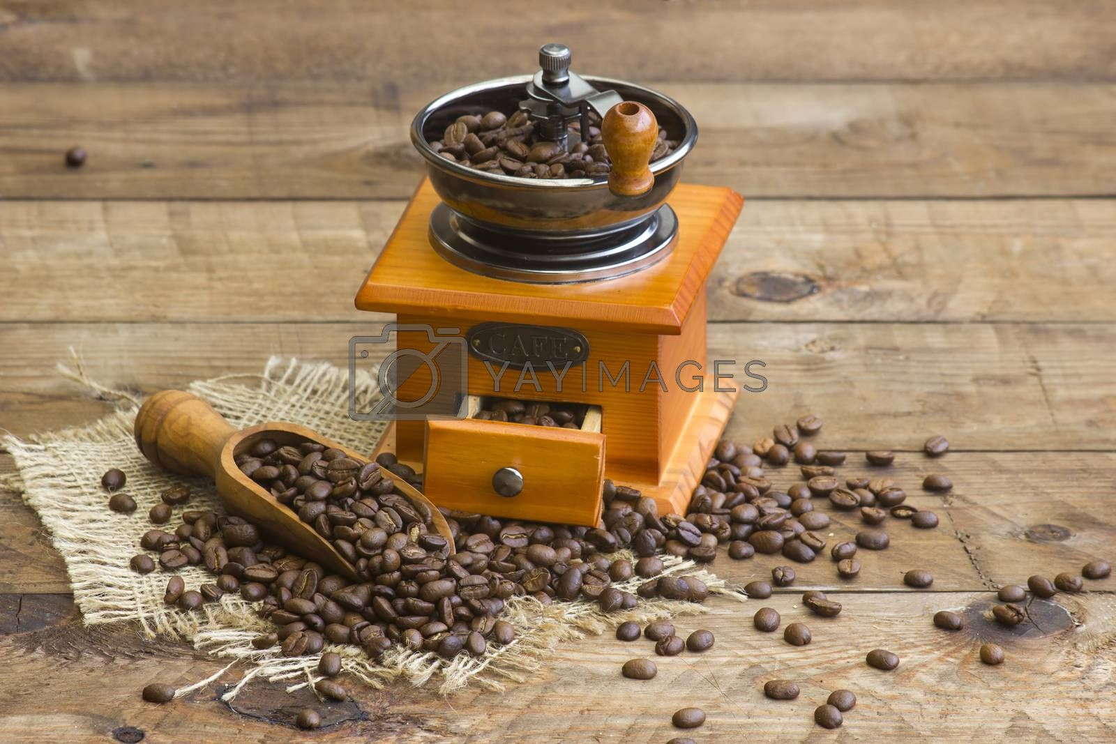 coffee grinder on wooden background with roasted coffee beans by miradrozdowski