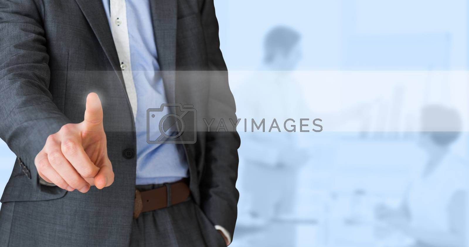 Businessman in grey suit pointing against blue background