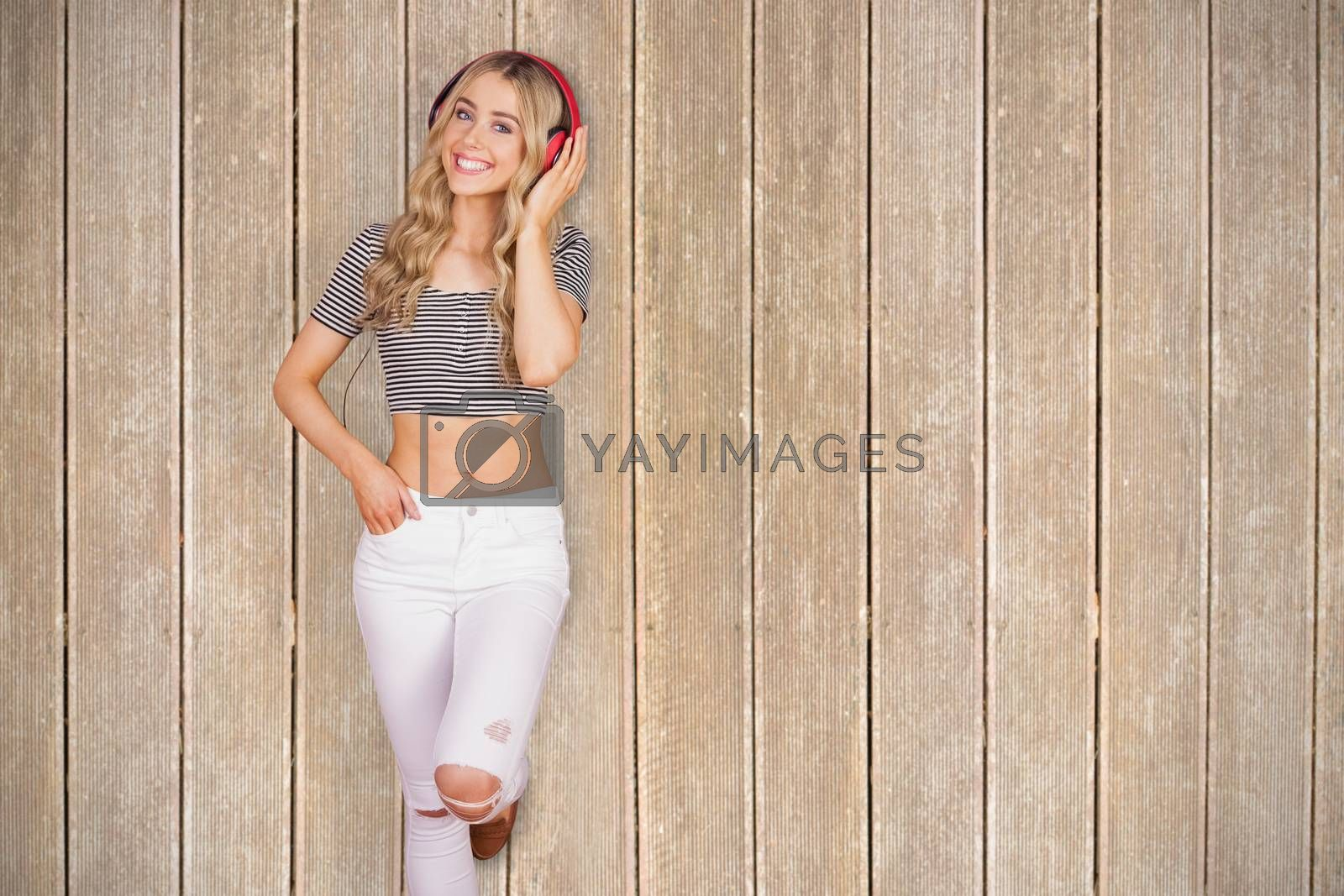 Portrait of a pretty young woman with headphones  against wooden planks