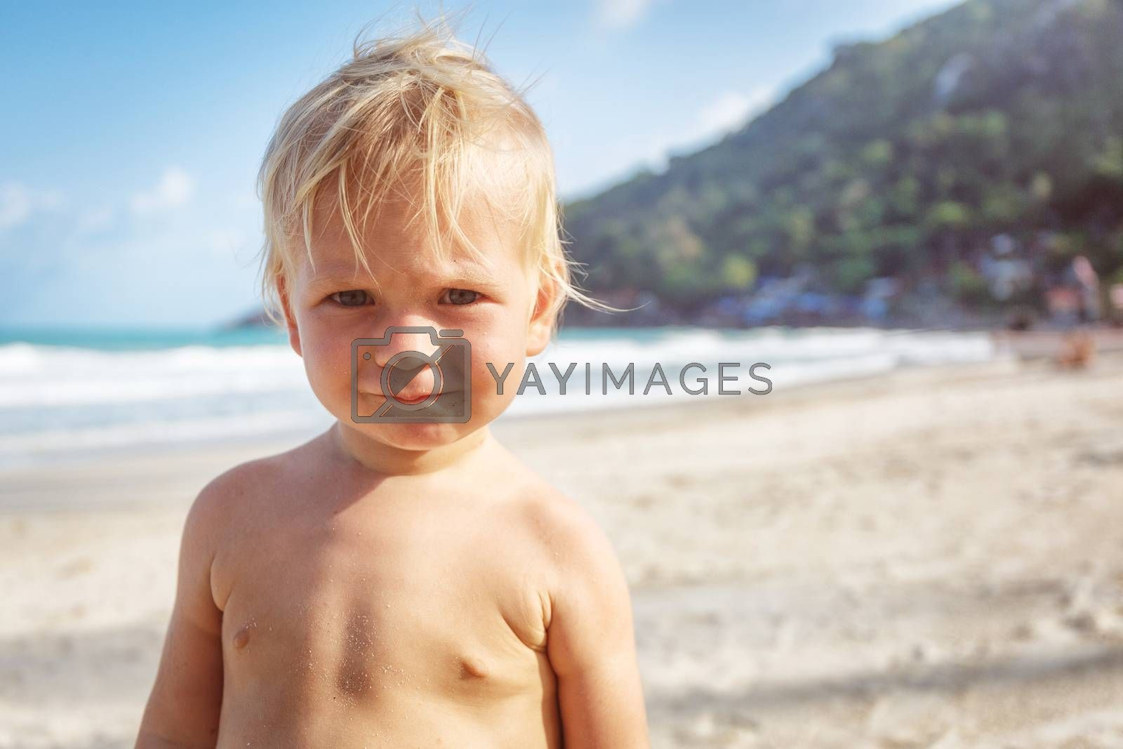 Portrait of a baby with a naked torso on the beach