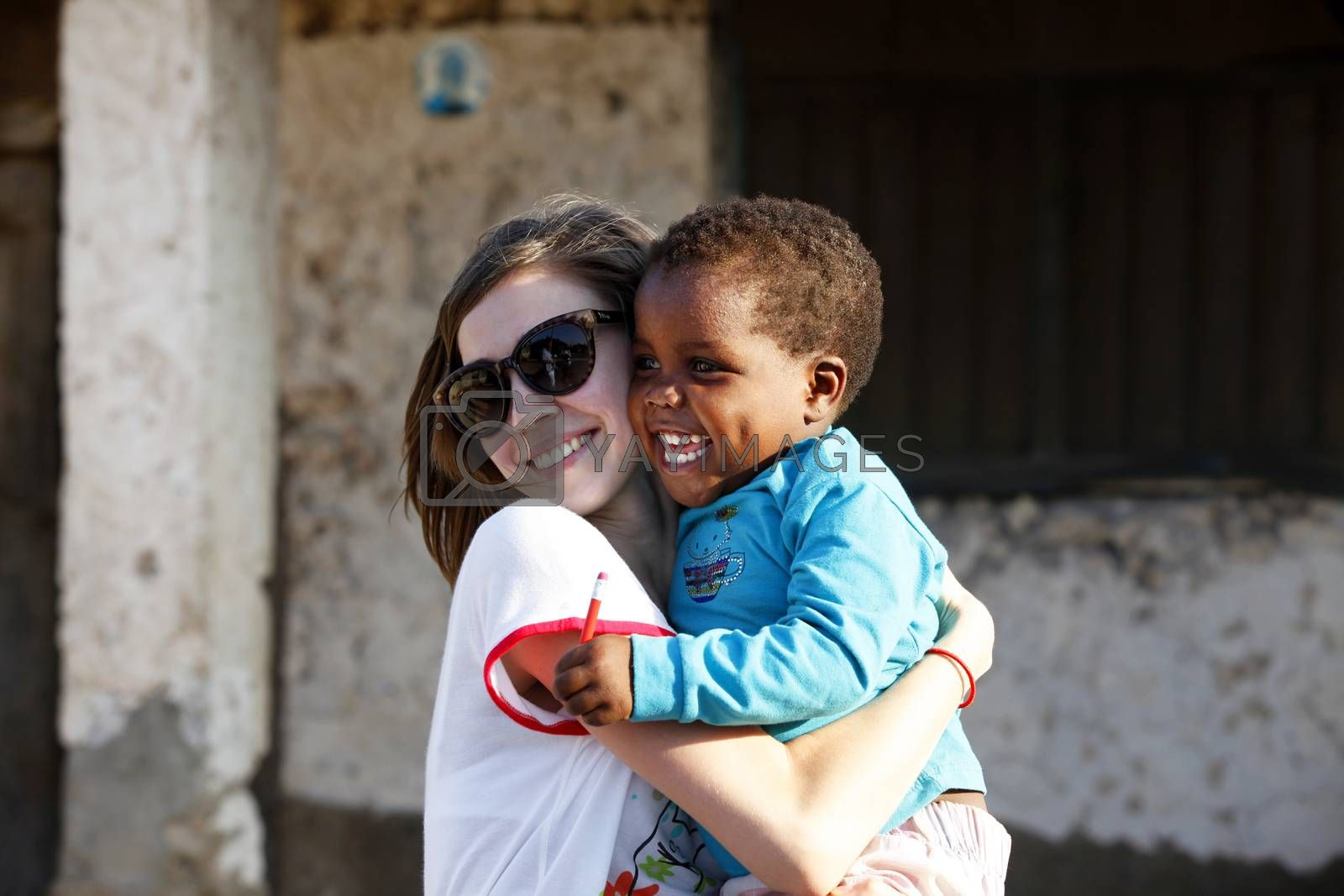Zanzibar, Tanzania - January 8, 2016: Young woman - a tourist from Russia holds little African girl in her arms in Jambiani. Zanzibar