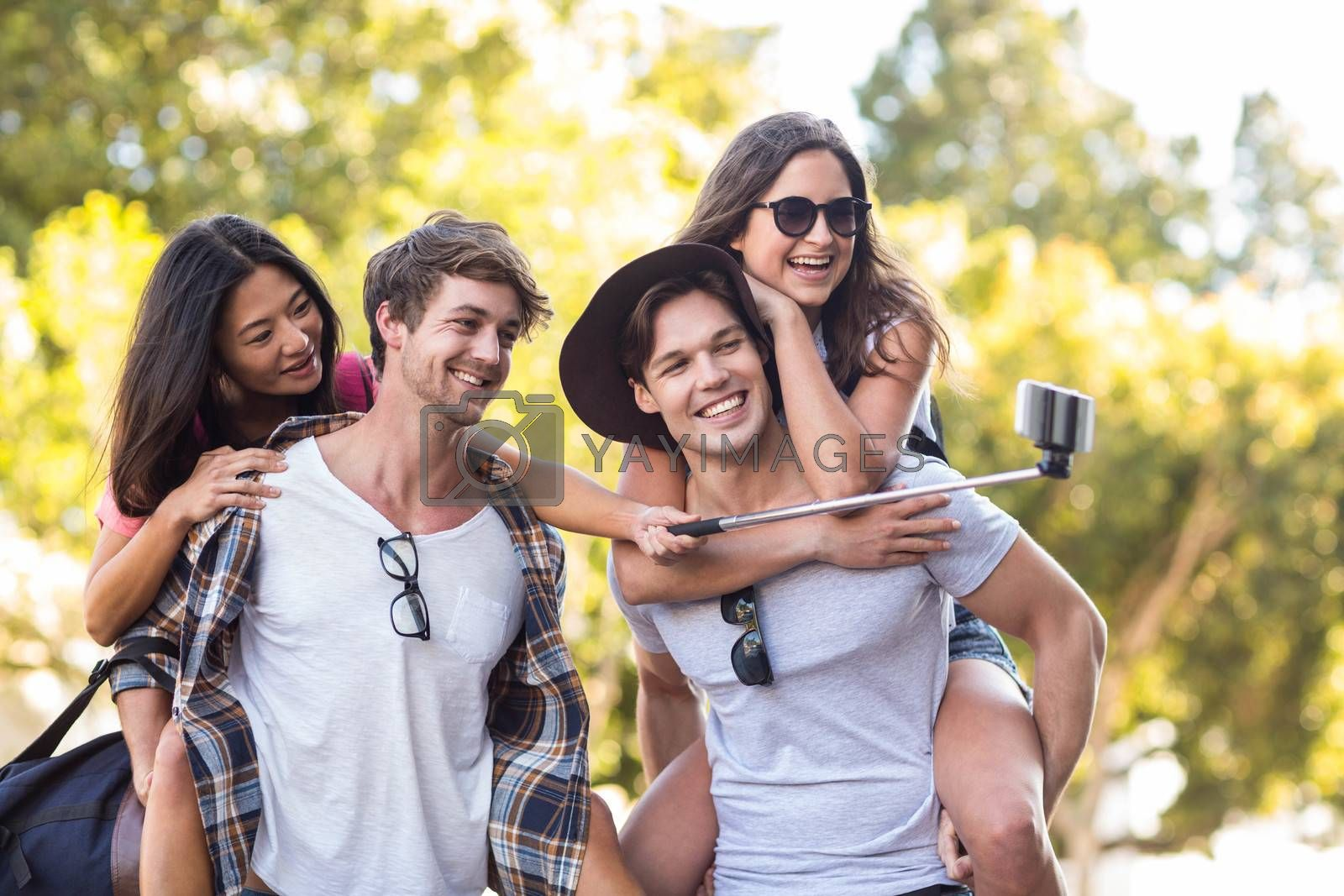 Hip men giving piggy back to their girlfriends and taking selfie on the street