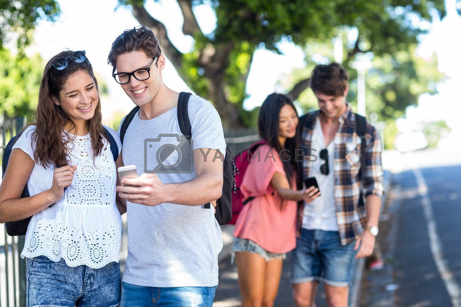 Hip couples checking at smartphone in the streets