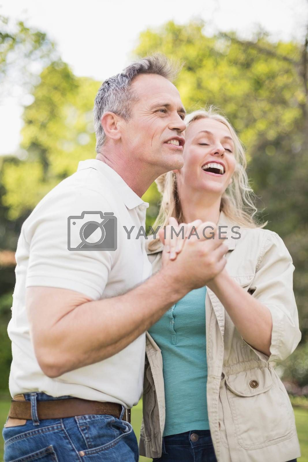 Cute couple dancing and holding hands outside