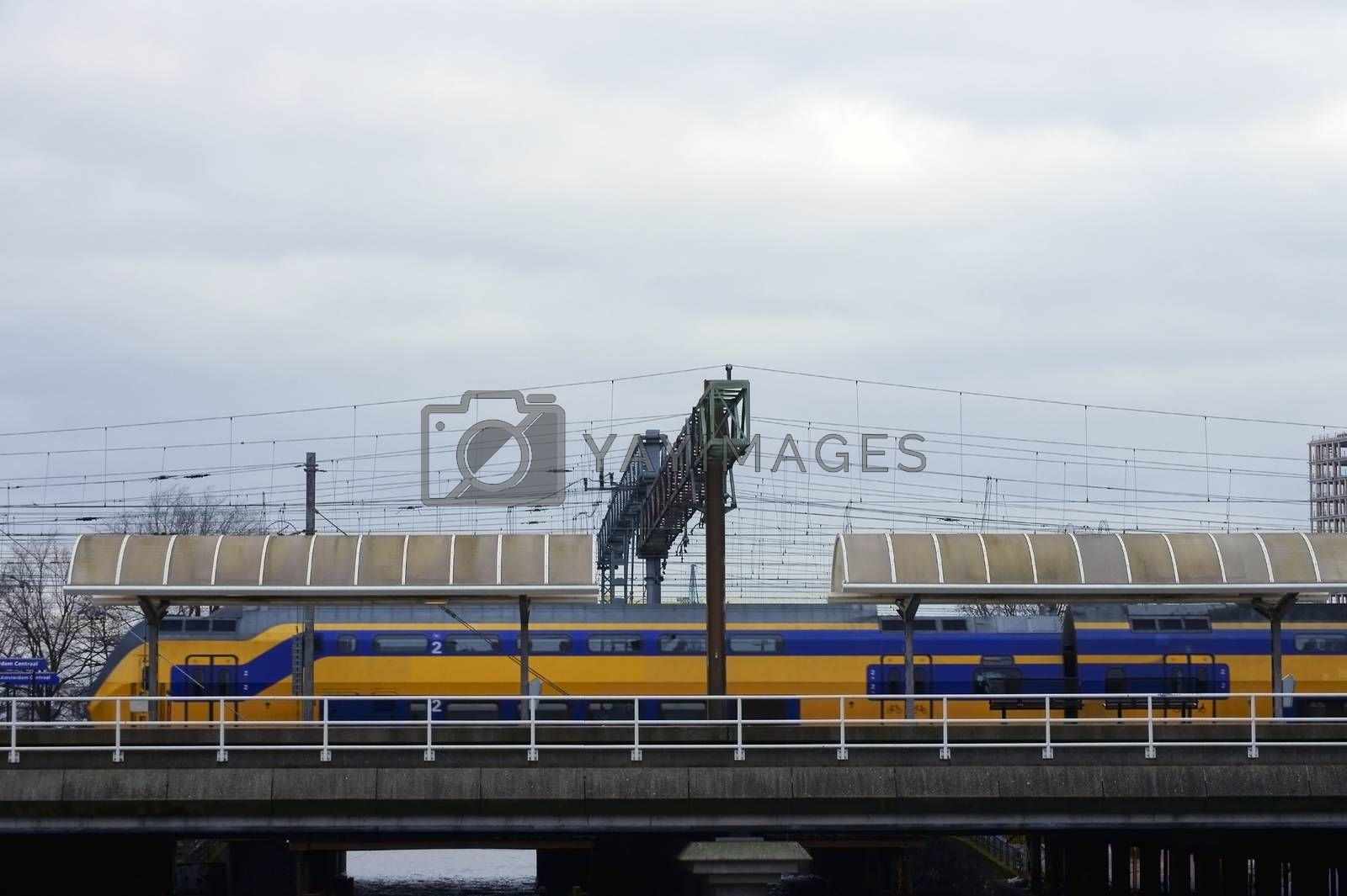 Amsterdam, Netherlands - December 30, 2014: A train crosses a bridge and stops at a station on the Port of Amsterdam outside the main railway station on December 30, 2014 in Amsterdam.