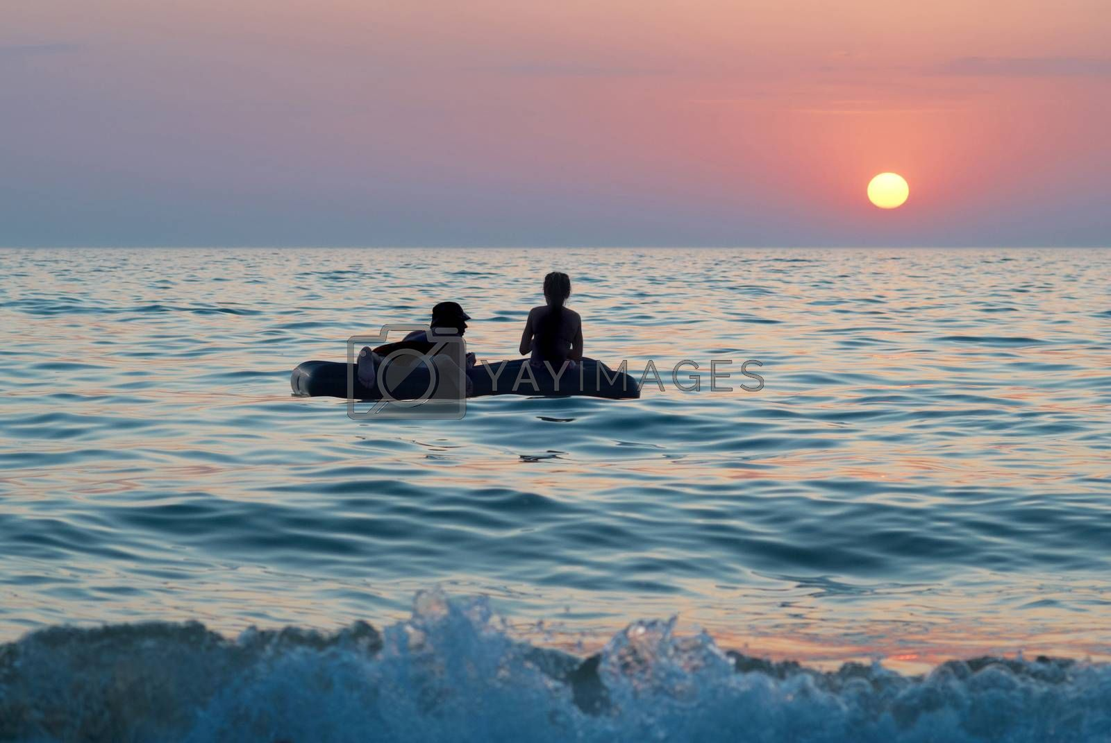 People on the raft with sea's sunset