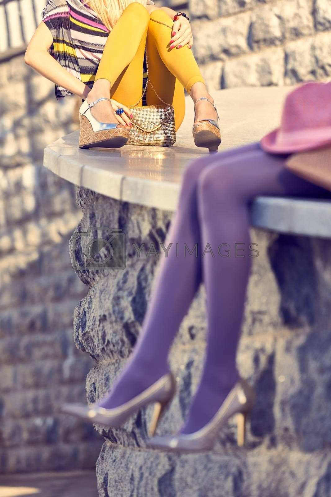 Fashion urban beauty people friends,outdoor.Womens sexy legs, pantyhose, stylish shoes, clutches.Playful hipster girls in trendy dresses.Stone wall background.Creative unusual. Vivid party lifestyle