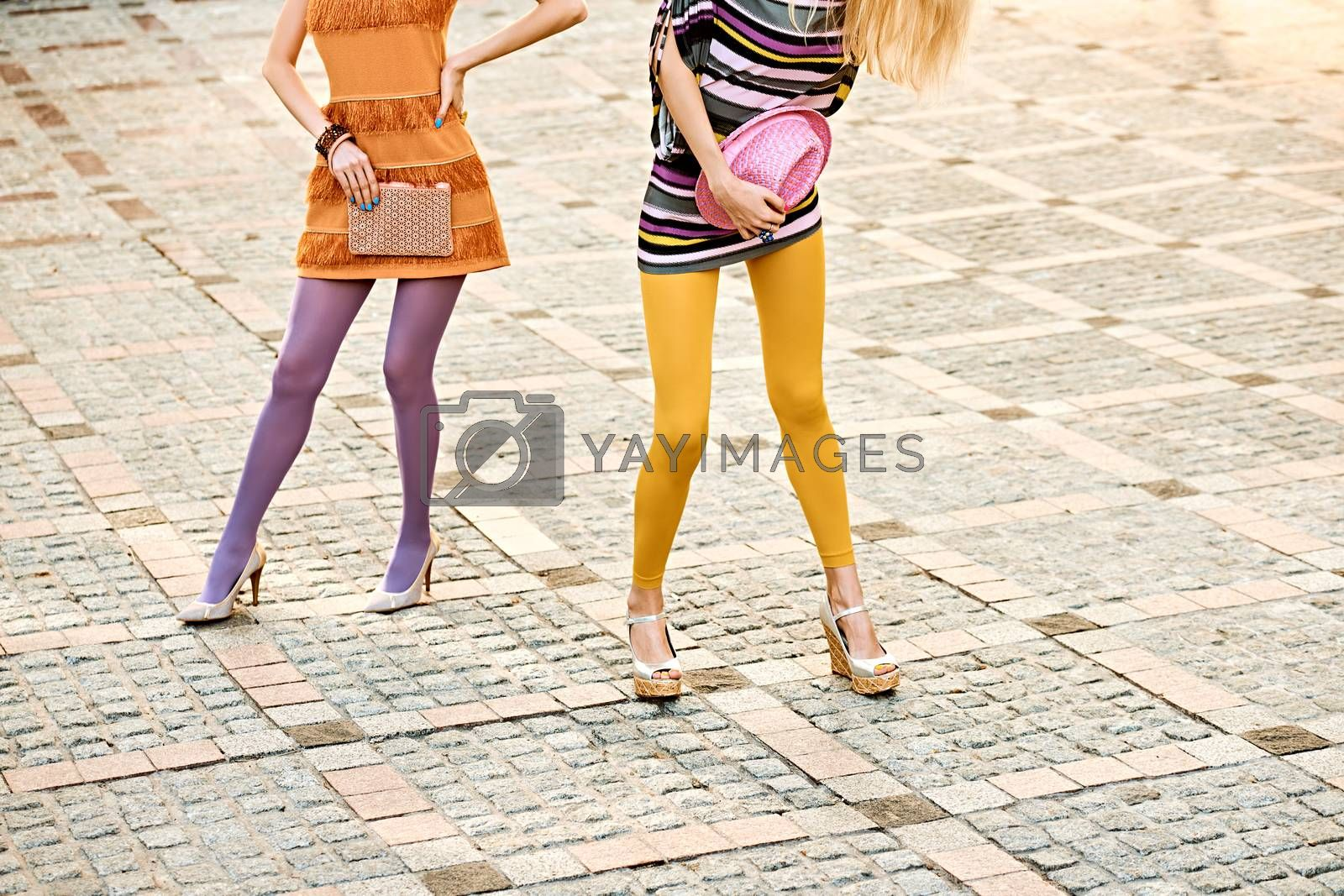 Fashion urban beauty people,friends, outdoor.Womens sexy legs, pantyhose, stylish shoes,clutch, hat.Playful hipster girls in trendy dresses on paving stone, creative unusual pose.Vivid disco lifestyle