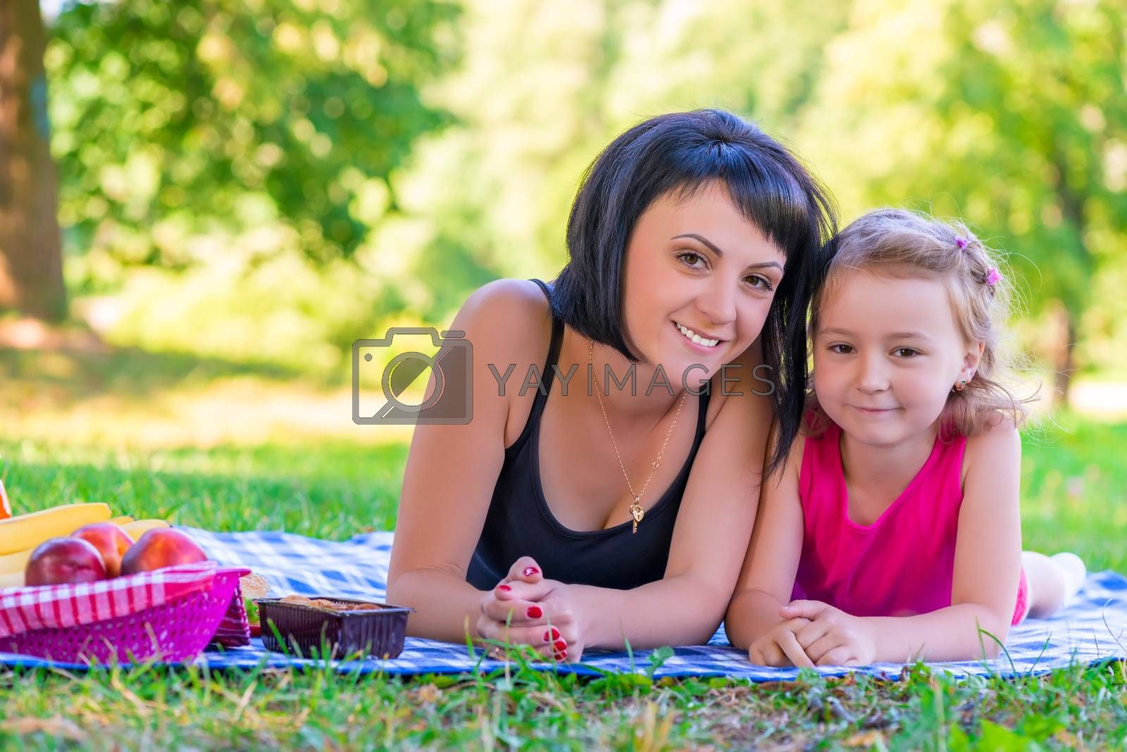 portrait of a smiling mother and her daughter on the lawn