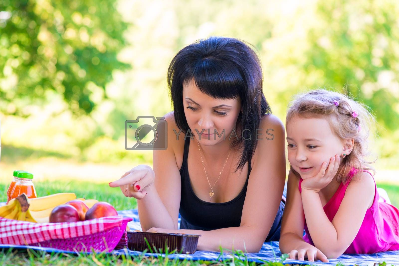 Mom showing her daughter at a picnic fruit