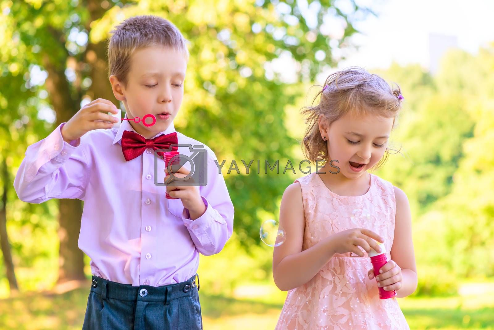 boy and a girl of 6 years on the meadow with bubbles