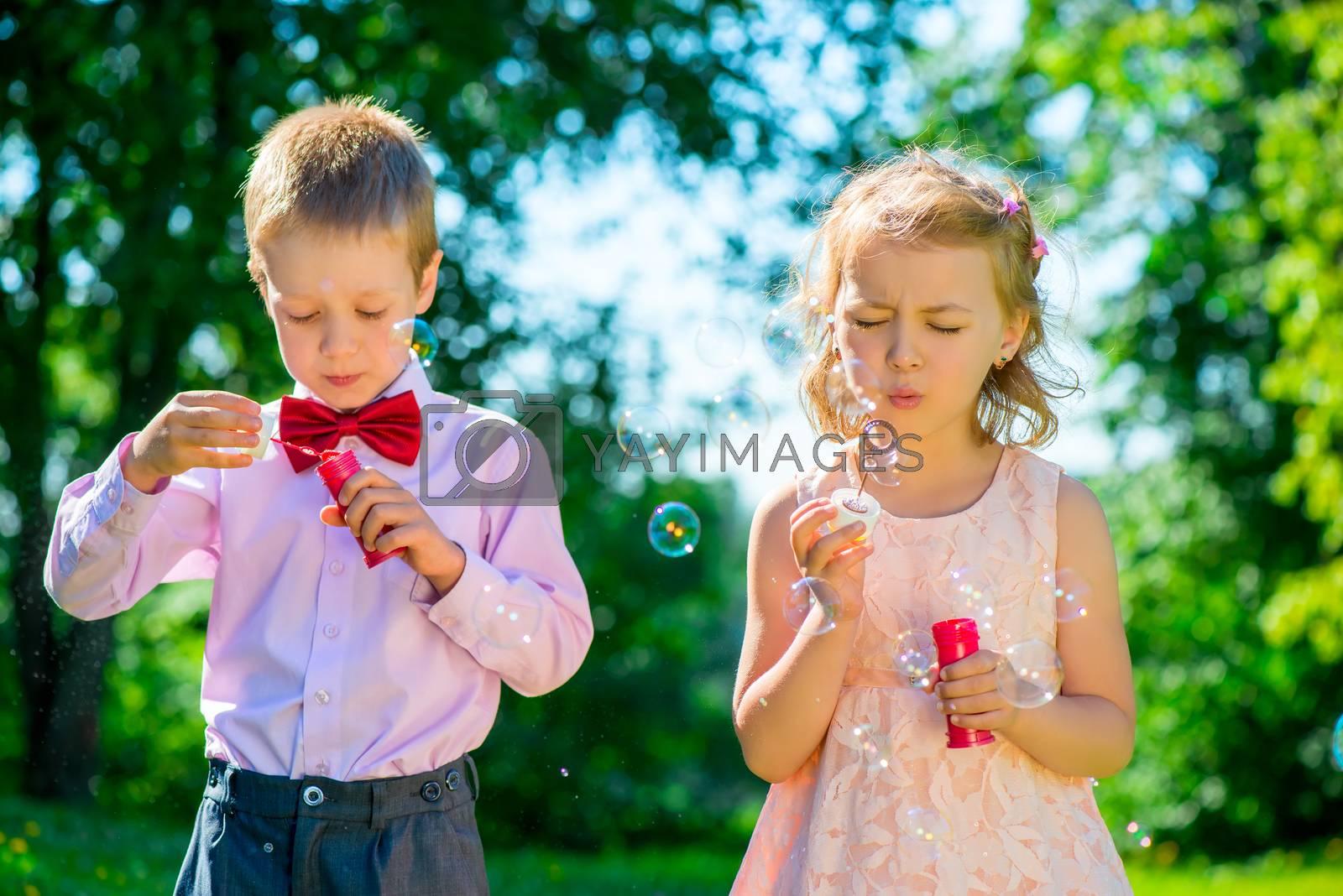 happy children doing soap bubbles outdoors