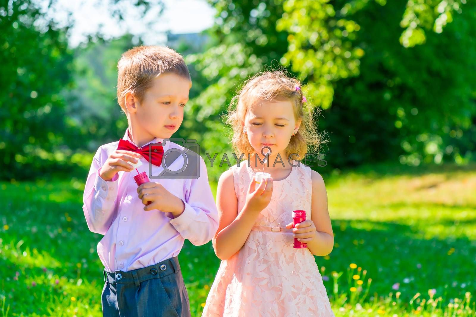 six year old boy looks at the girl makes soap bubbles