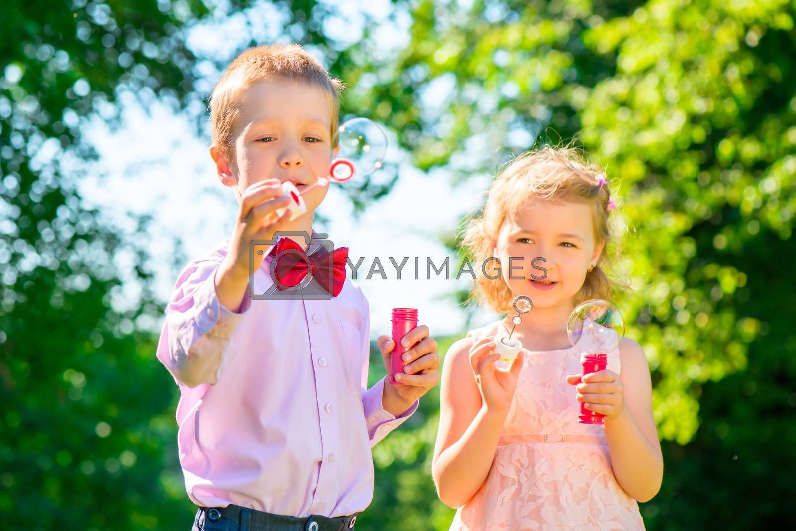 little friends in the summer park with soap bubbles
