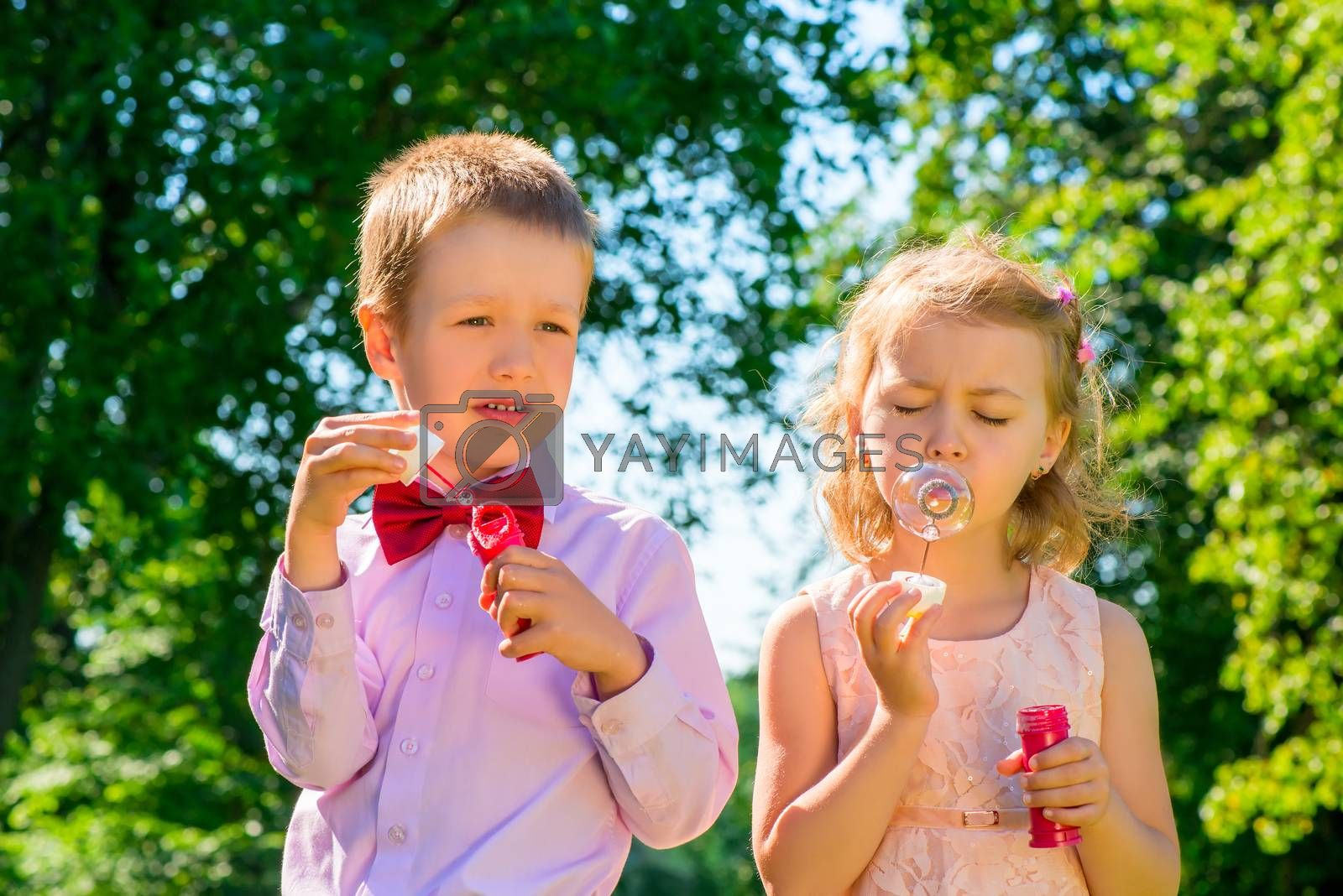 beautifully dressed kids with soap bubbles in the park