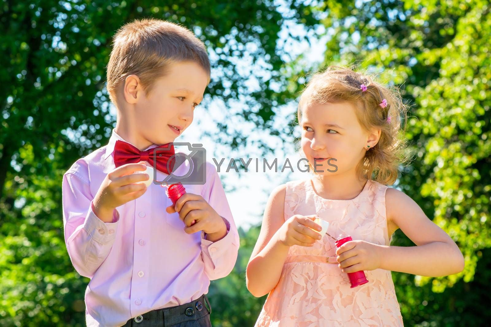 Happy laughing children doing soap bubbles