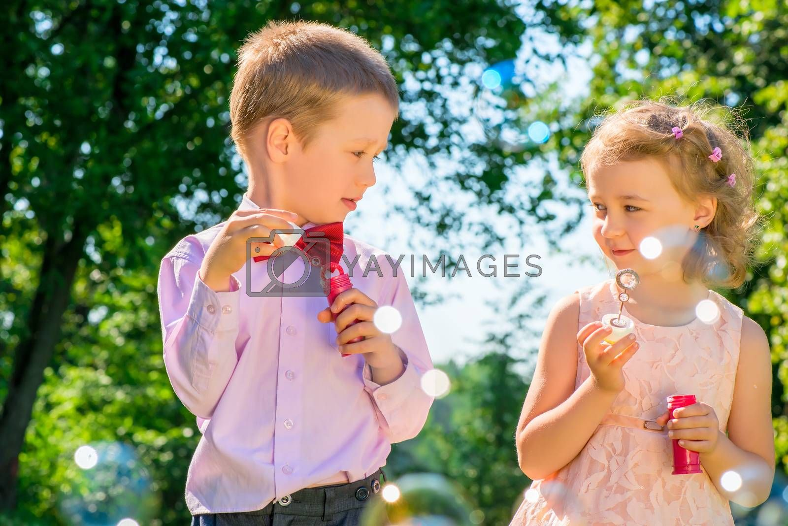 portrait of children with soap bubbles outdoors in the park