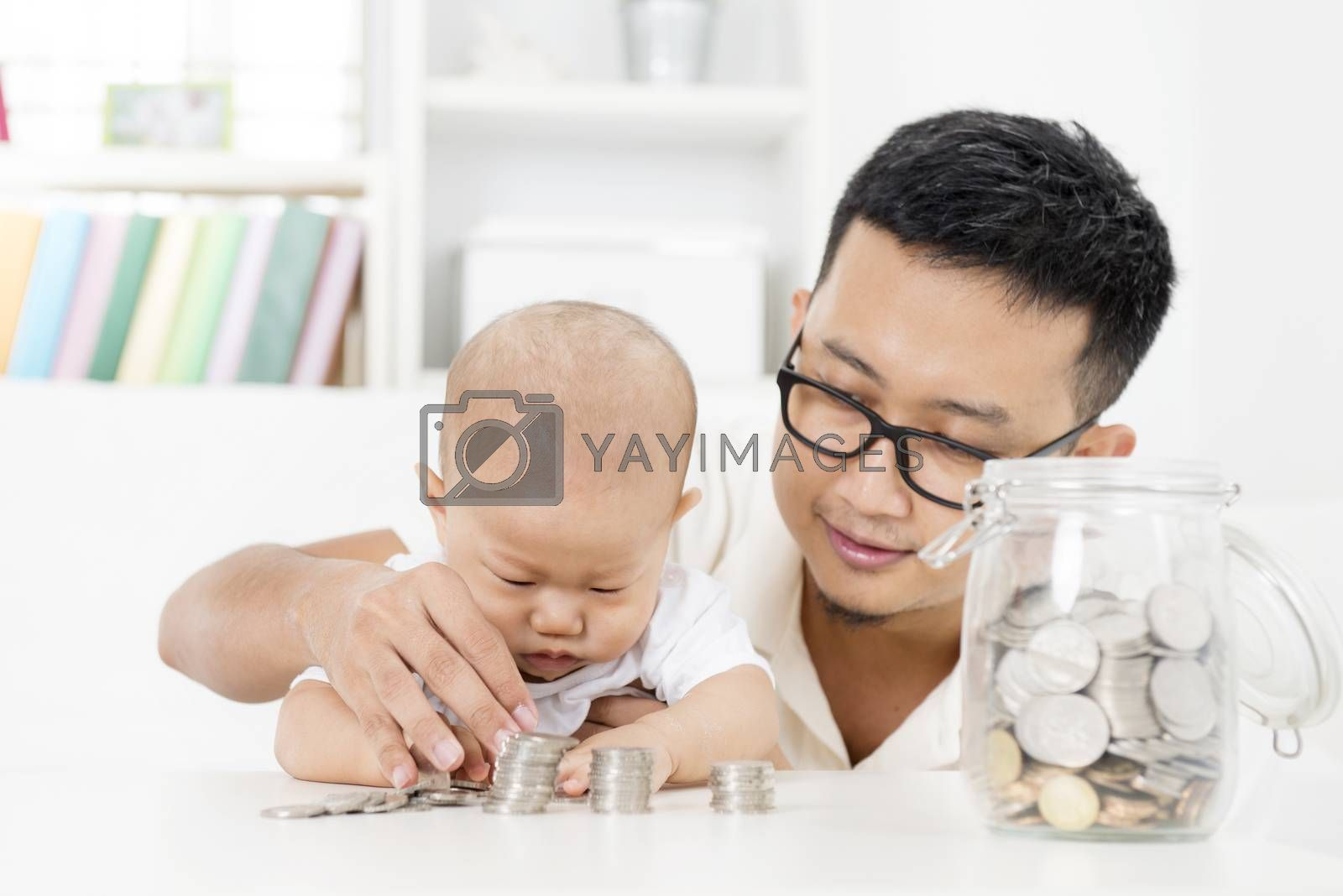 Asian family lifestyle at home. Father and baby counting coins, future education planning concept.