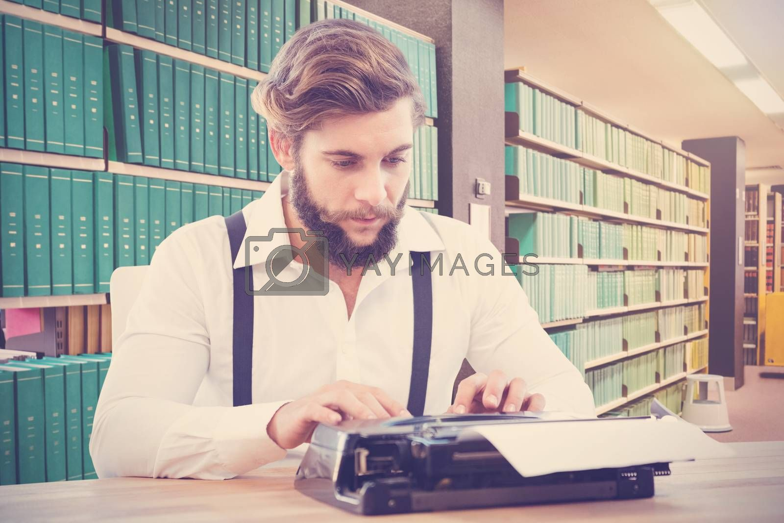 Hipster working on typewriter against close up of a bookshelf