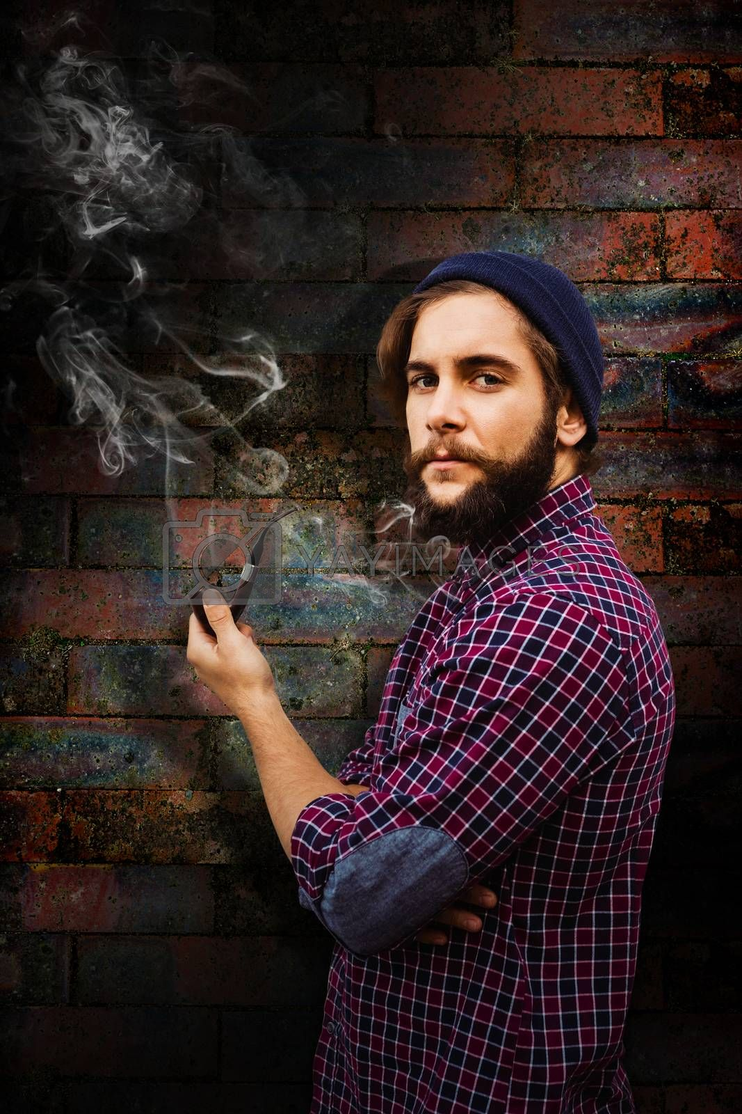 Side view of hipster holding smoking pipe against texture of bricks wall