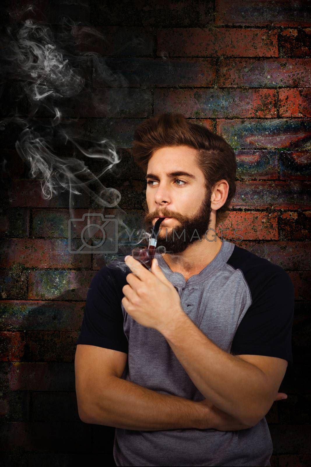 Confident hipster smoking pipe against texture of bricks wall