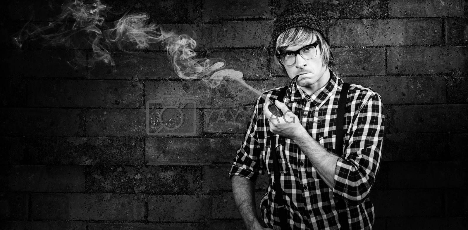 Serious blond hipster smoking a pipe against texture of bricks wall