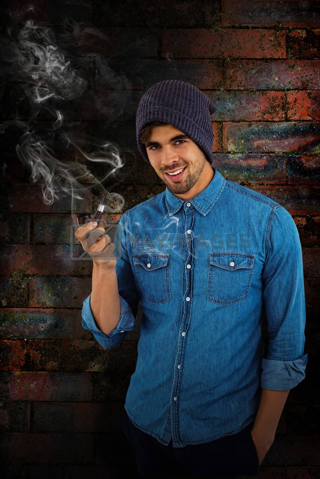 Portrait of hipster smiling while holding smoking pipe against texture of bricks wall