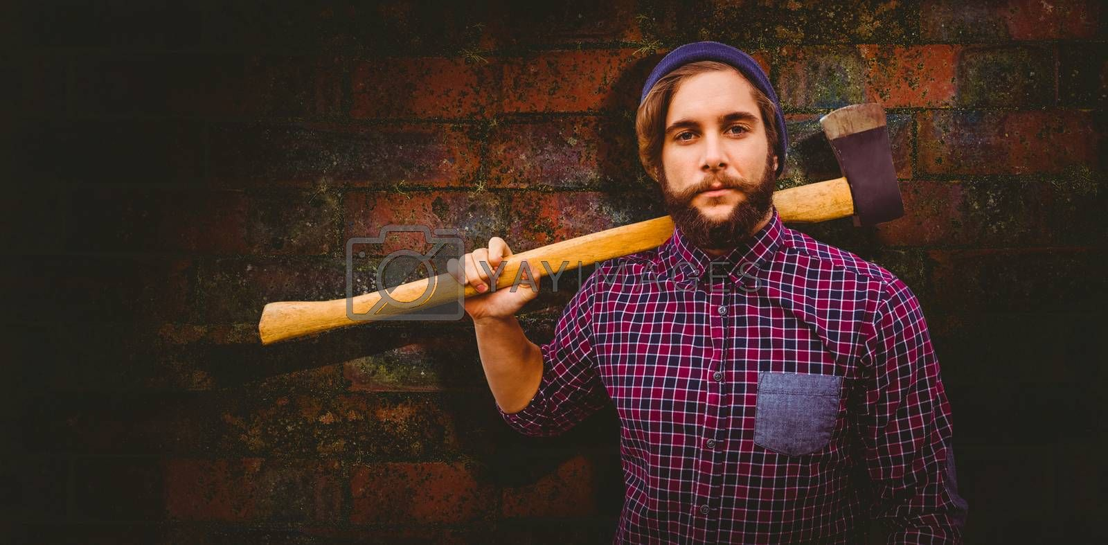 Hipster holding axe on shoulder against texture of bricks wall
