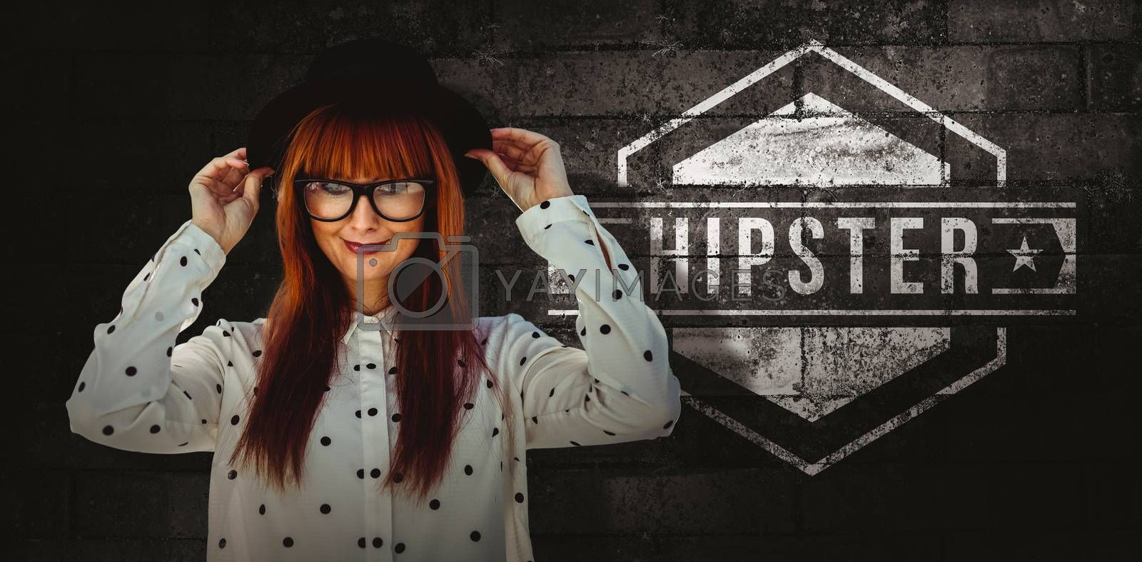 Attractive smiling hipster woman with hat  against texture of bricks wall