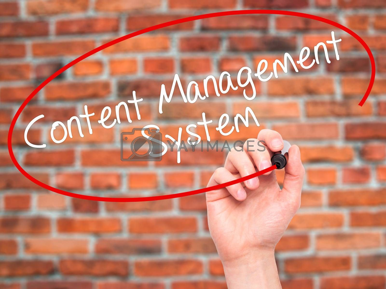Man Hand writing Content Management System  with black marker on visual screen. Isolated on bricks. Business, technology, internet concept. Stock Photo