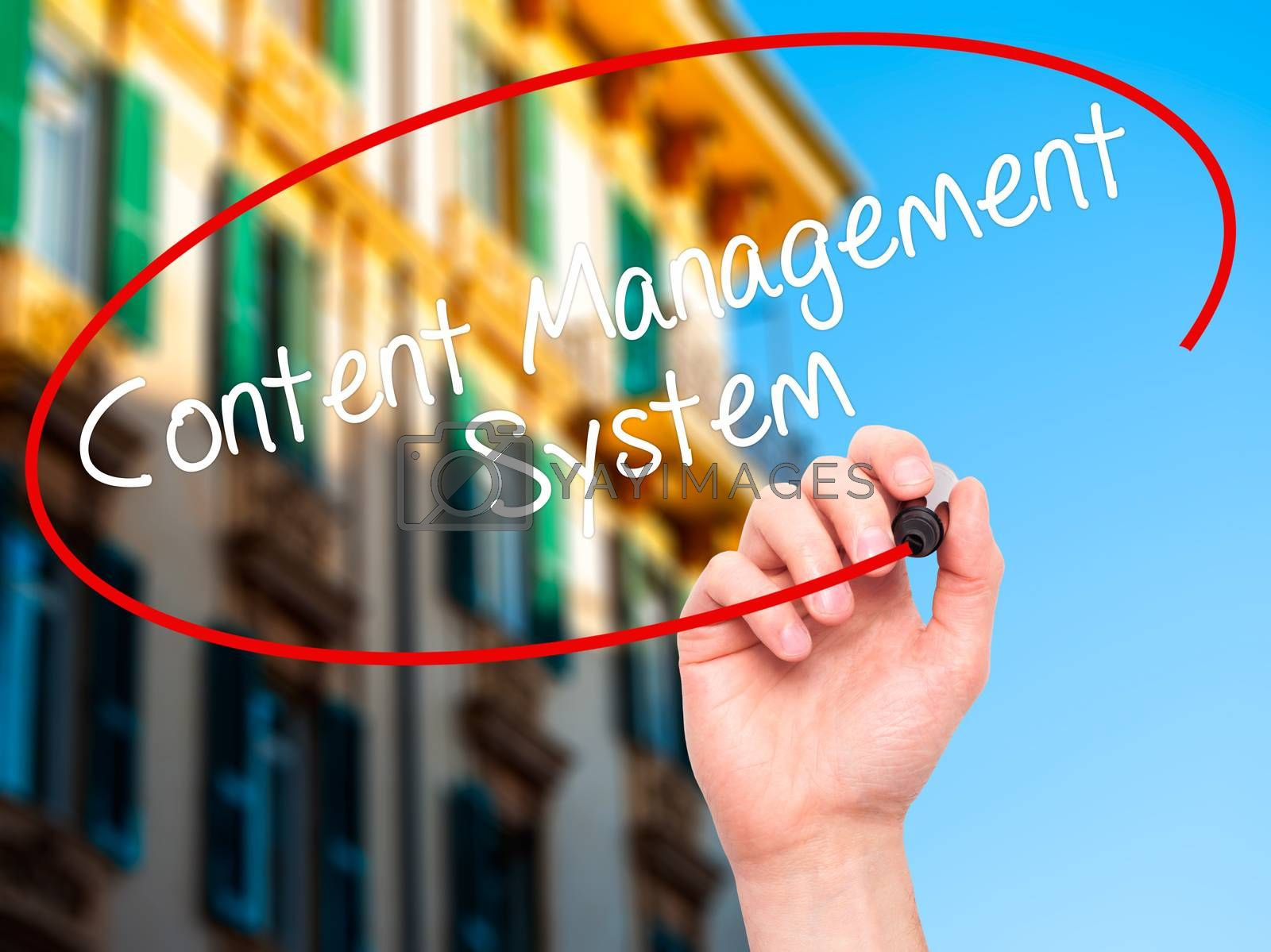 Man Hand writing Content Management System  with black marker on visual screen. Isolated on city. Business, technology, internet concept. Stock Photo