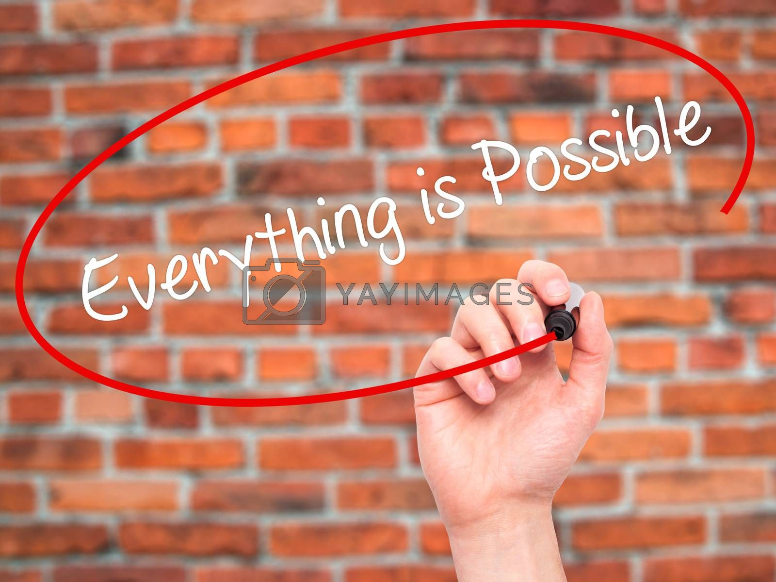 Man Hand writing Everything is Possible with black marker on visual screen. Isolated on bricks. Business, technology, internet concept. Stock Photo