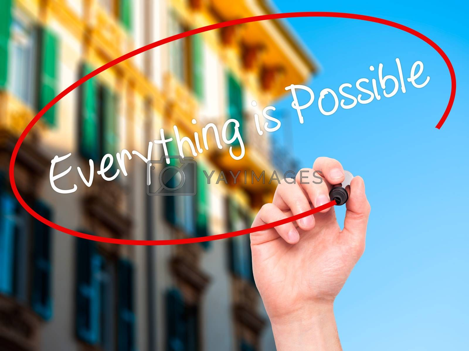 Man Hand writing Everything is Possible with black marker on visual screen. Isolated on city. Business, technology, internet concept. Stock Photo