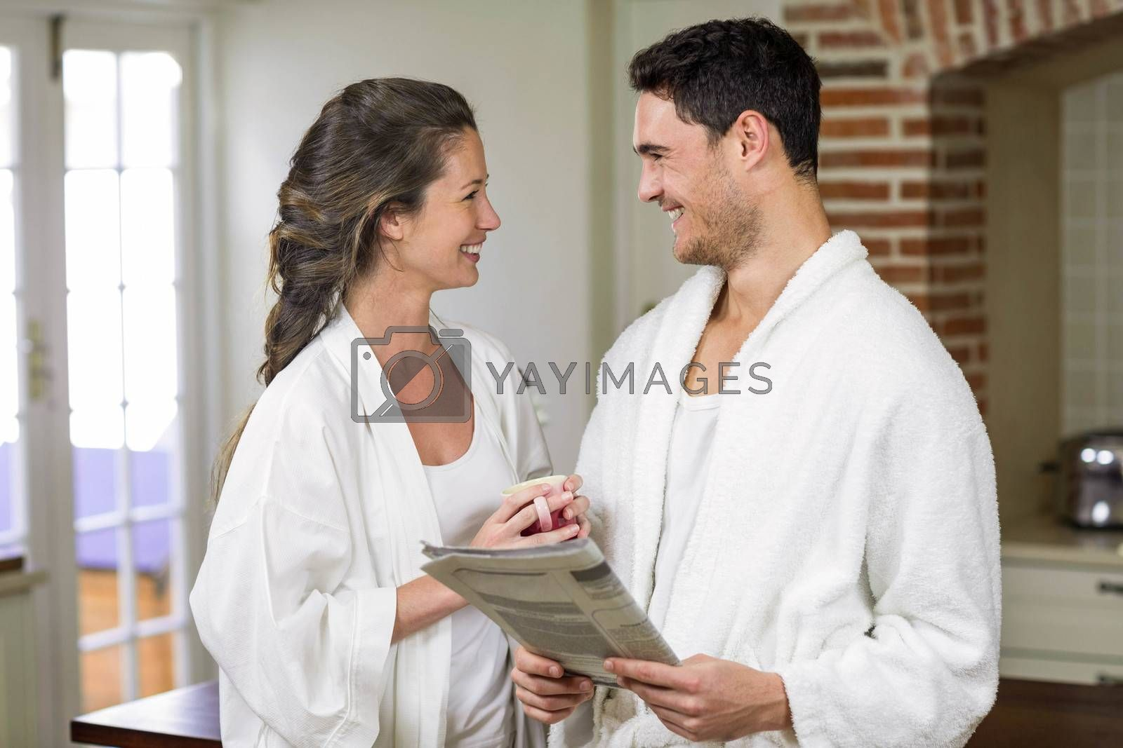 Happy couple in bathrobe reading newspaper in the kitchen