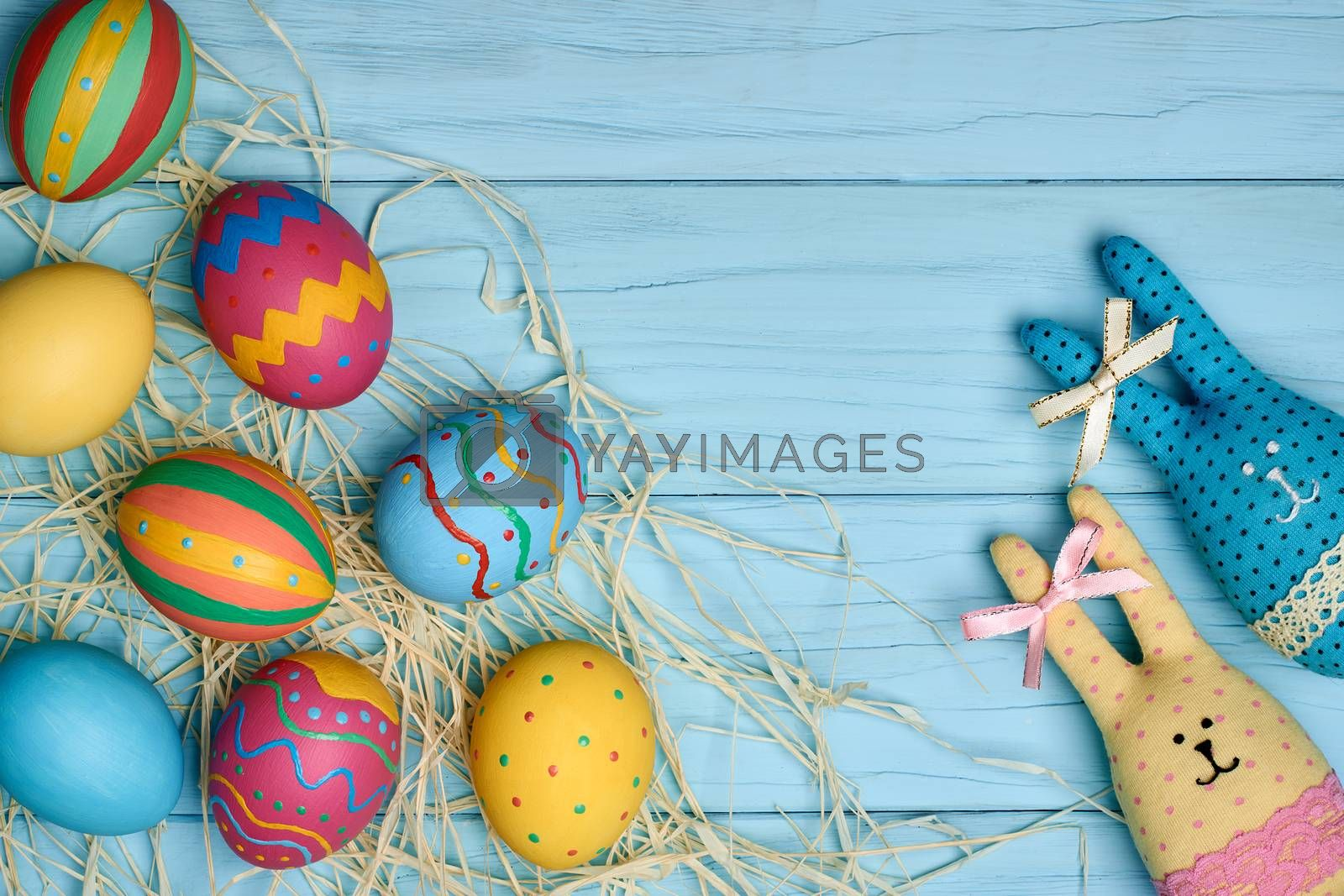 Easter eggs and rabbits. Happy bunny handmade and hand painted multicolored decorated eggs on green straw nest, blue wooden background, copyspace. Unusual creative holiday greeting card