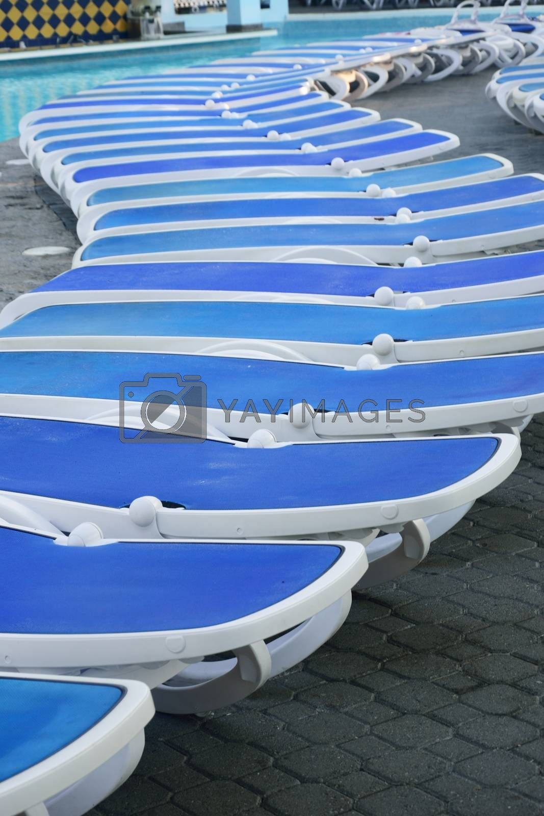 Long row of Empty Sunbeds by pool