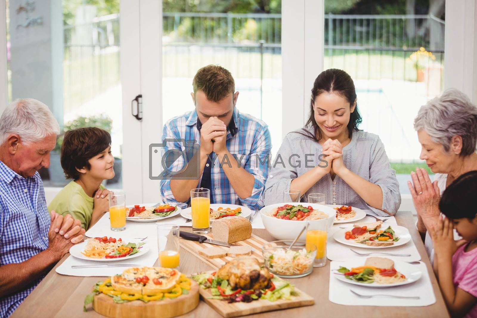 Family praying together before meal by Wavebreakmedia