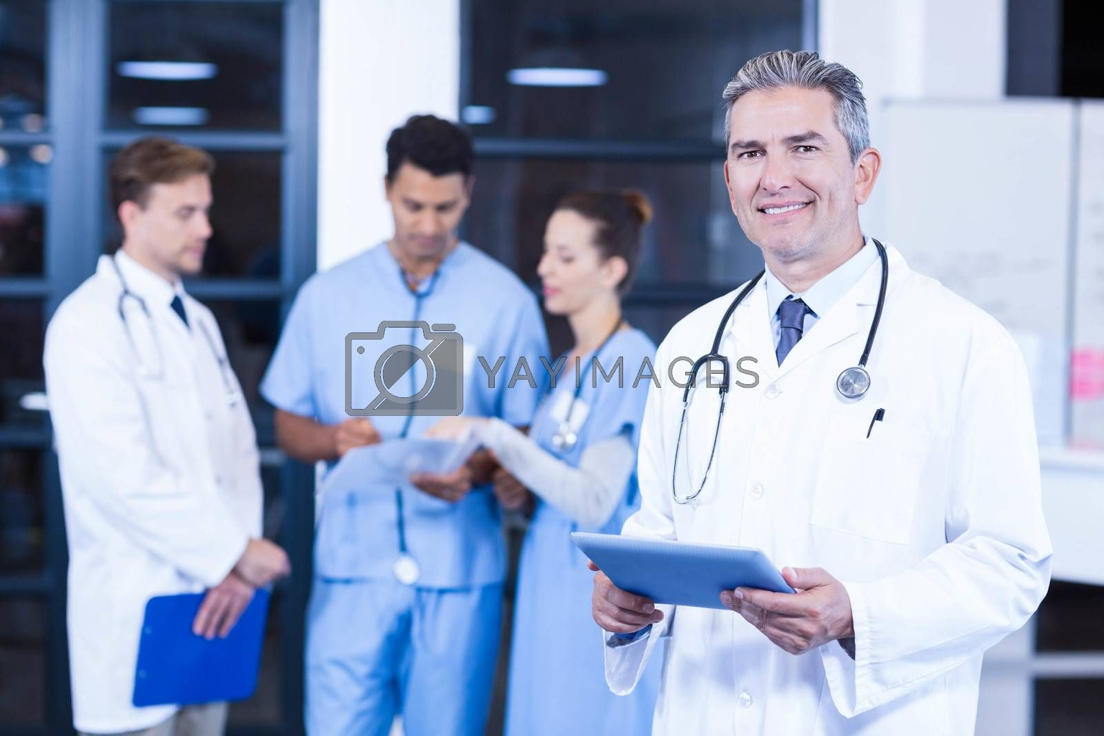 Doctor holding digital tablet and smiling at camera while his colleagues discussing in background