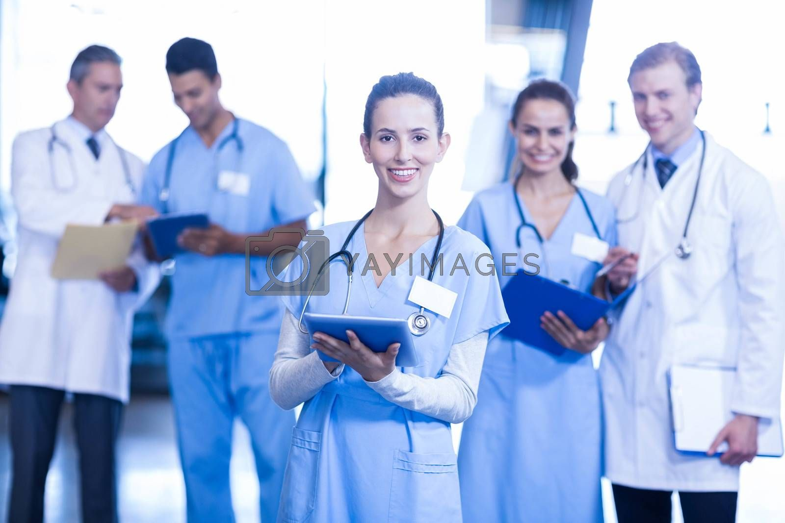 Female doctor using tablet and smiling at camera while her colleagues standing in background