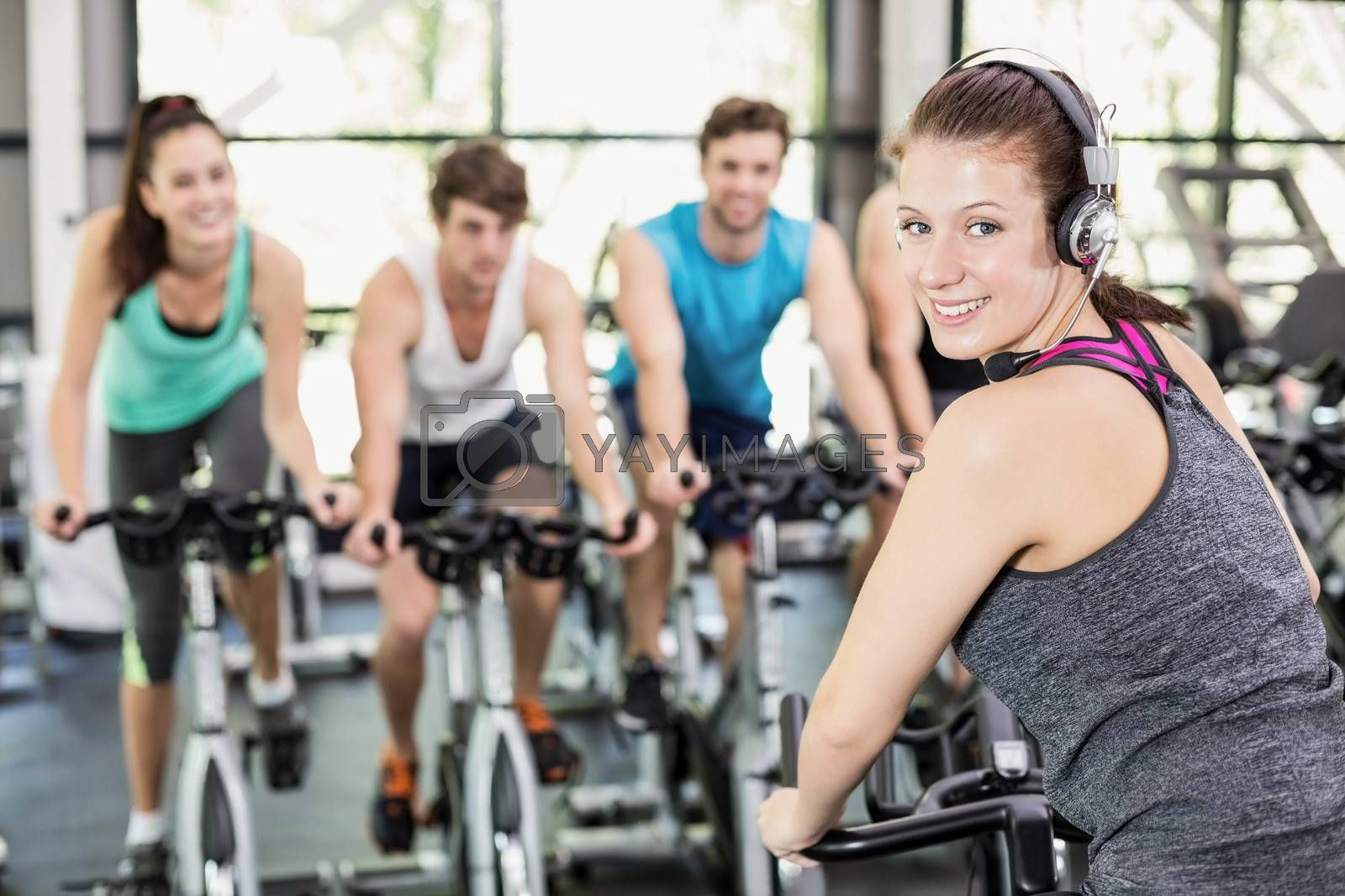 Fit group of people using exercise bike together in crossfit
