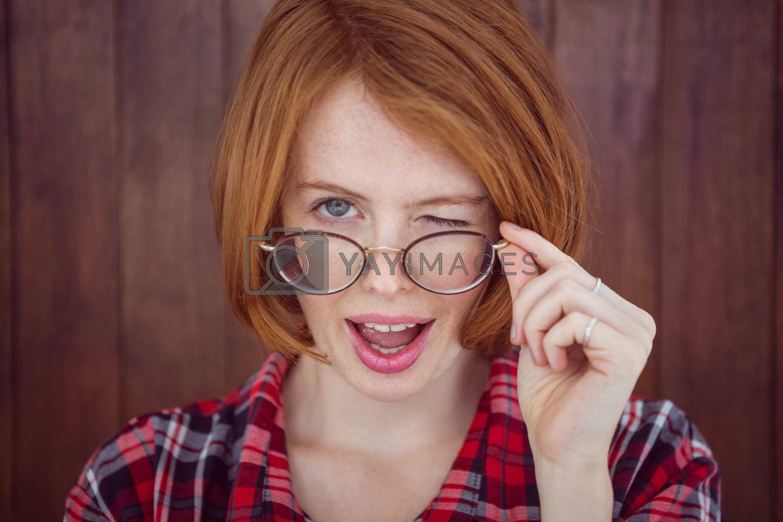 beautiful hipster woman, winking at the camera, against aa wooden background