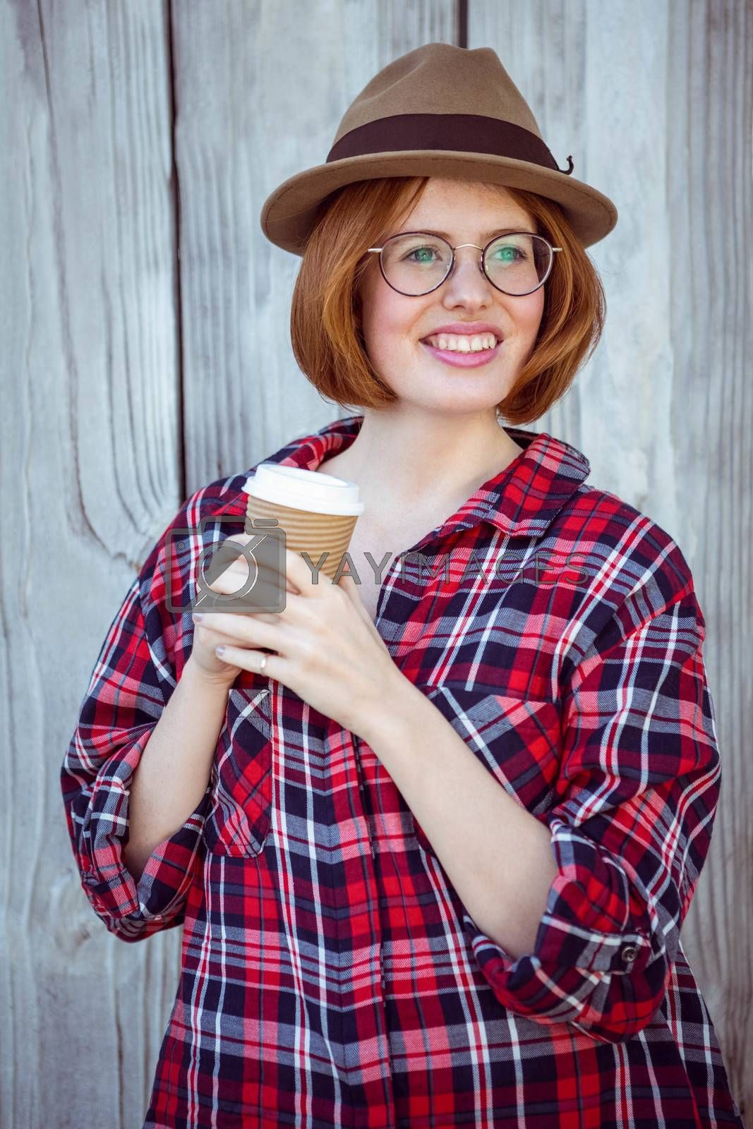 smiling hipster woman holding a coffee cup against a wooden background