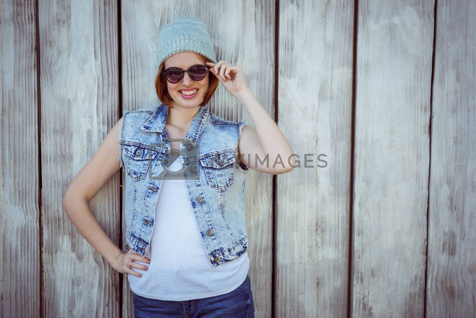 smiling hipster woman in sunglasses and a beanie hat against a wooden background
