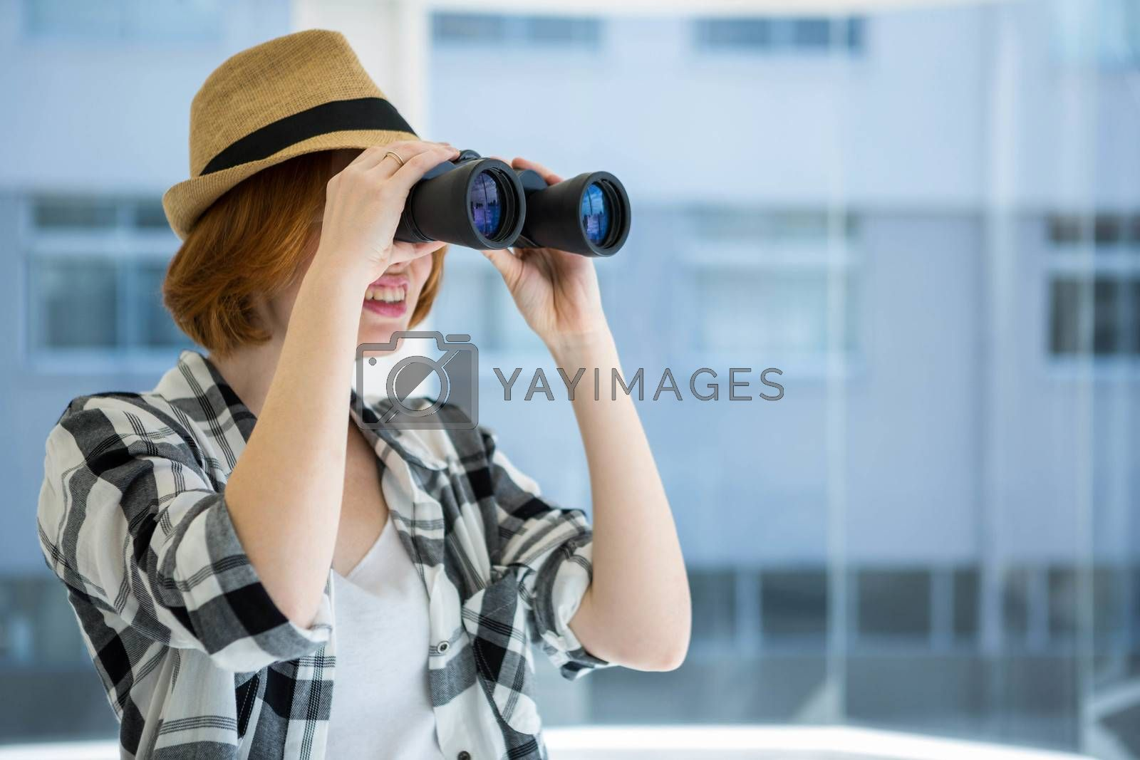 Red haired hipster looking through binoculars in front of a window