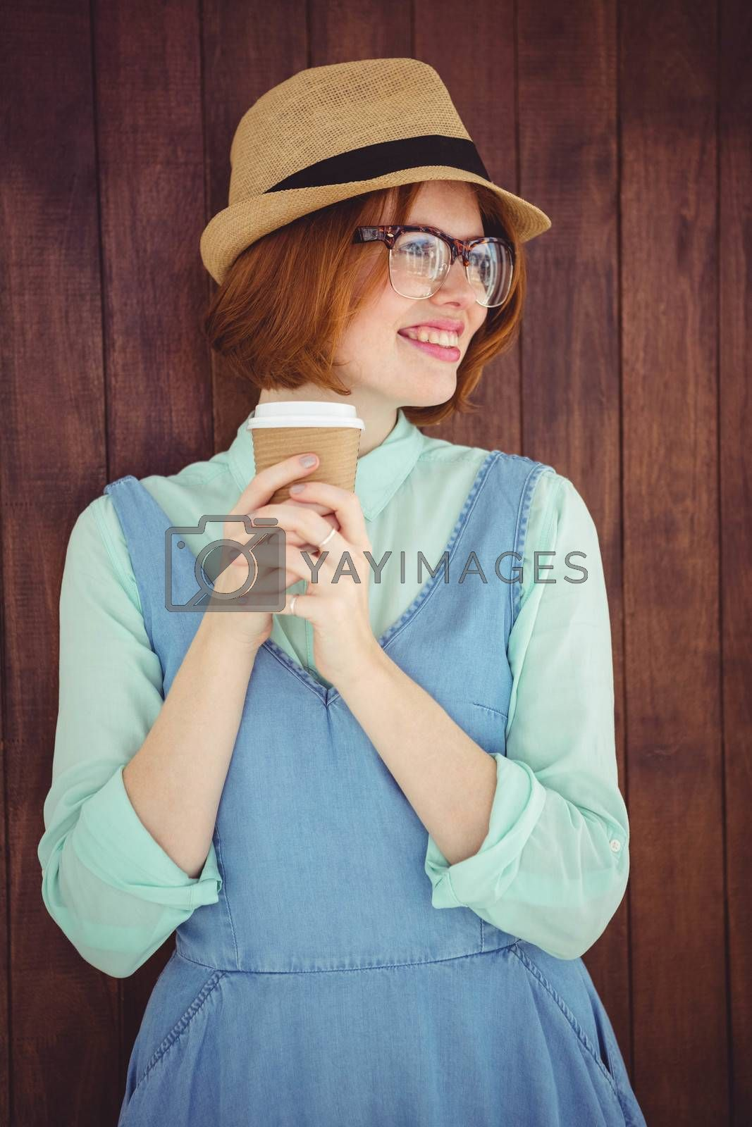 Cute red haired hipster with glasses holding disposable cup on wooden background